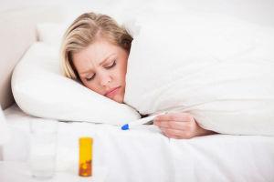 Больная женщина меряет температуру, для восстановления ей нужный общеукрепляющие витамины