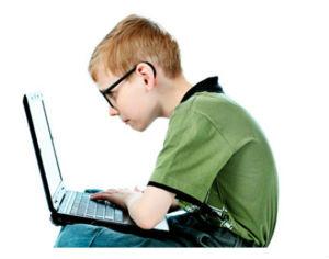 Ребенок с плохим зрением в очках сидит за компьютером